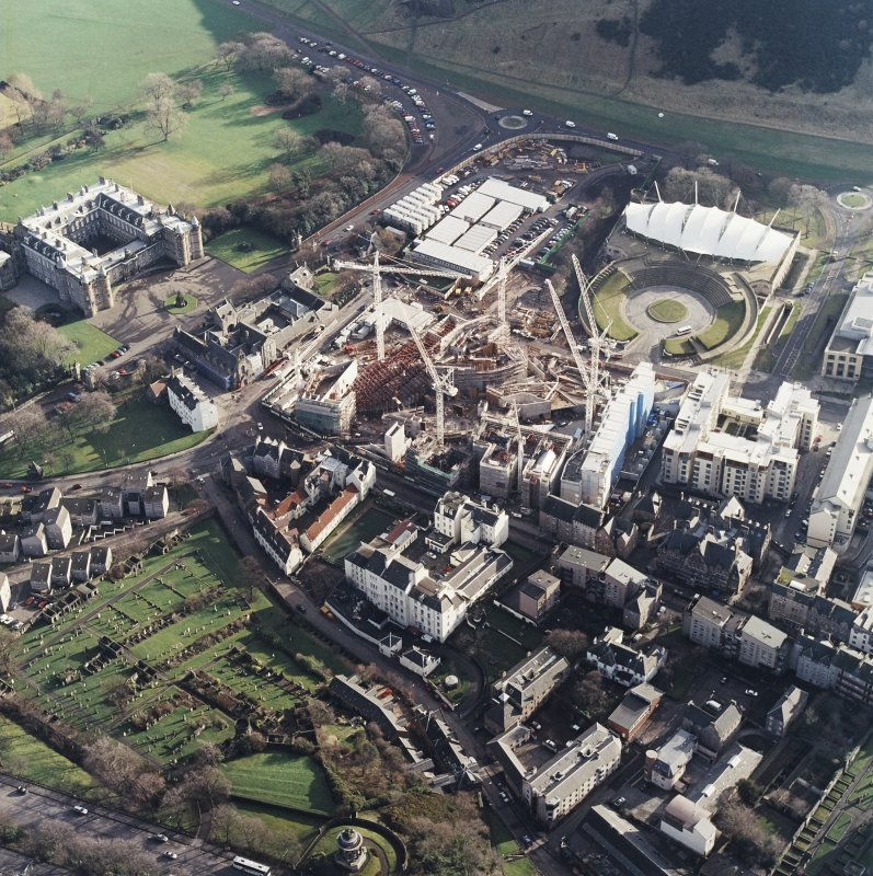 Oblique aerial view centred on the construction of the Scottish Parliament, with `Our Dynamic Earth', Queensberry House and Holyrood Palace adjacent, taken from the NW.