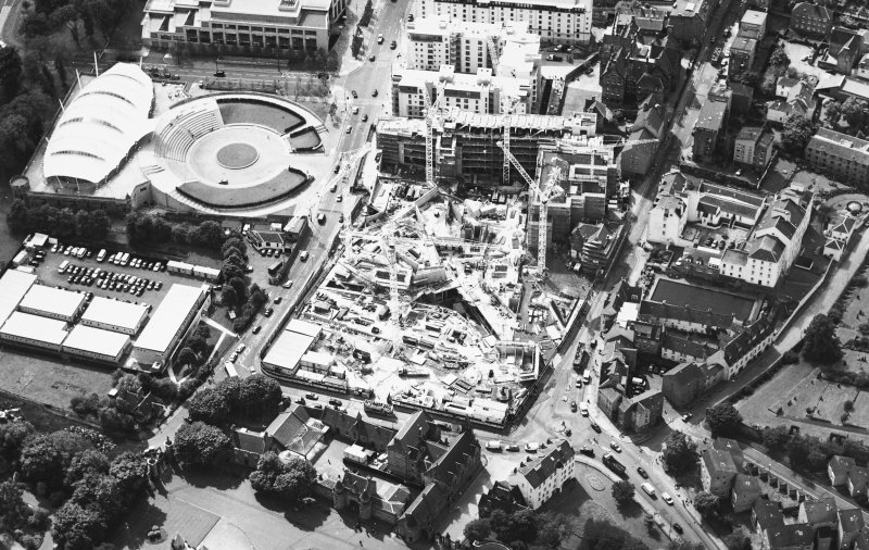 Oblique aerial view centred on the construction of the Scottish Parliament with the exhibition centre adjacent, taken from the ENE.