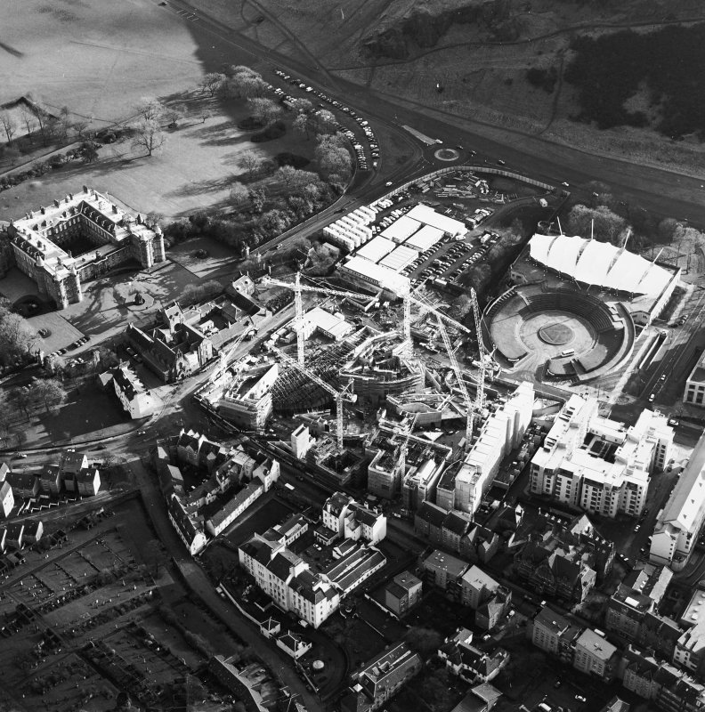 Oblique aerial view centred on the construction of the Scottish Parliament, with `Our Dynamic Earth¿, Queensberry House and Holyrood Palace adjacent, taken from the NW.