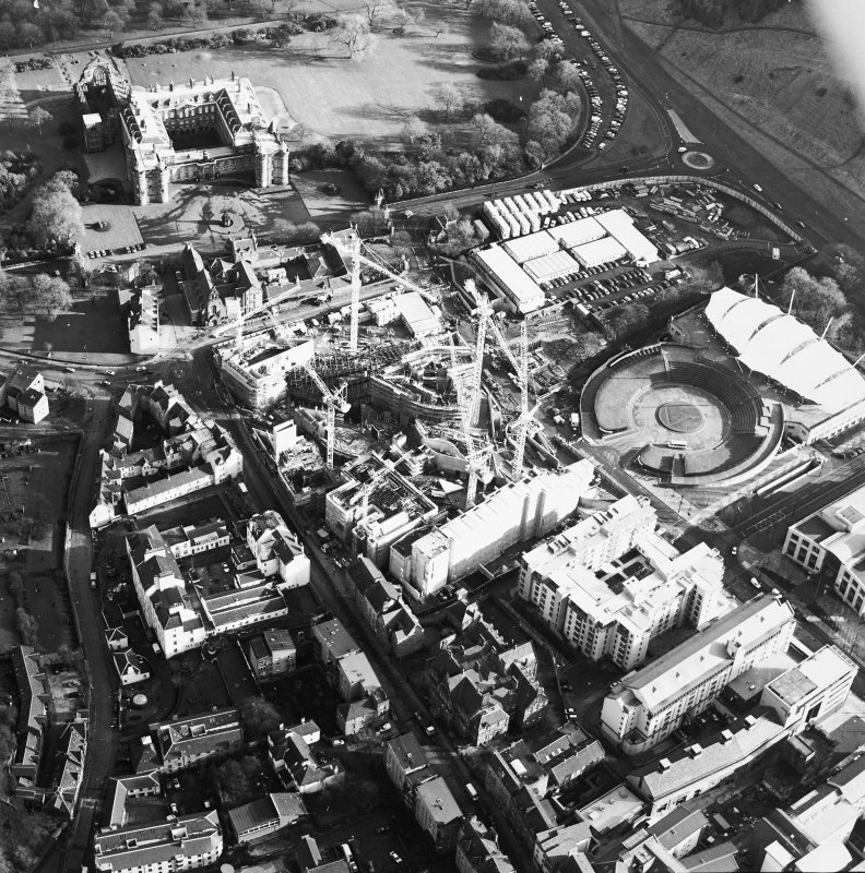 Oblique aerial view centred on the construction of the Scottish Parliament, with `Our Dynamic Earth', Queensberry House and Holyrood Palace adjacent, taken from the W.
