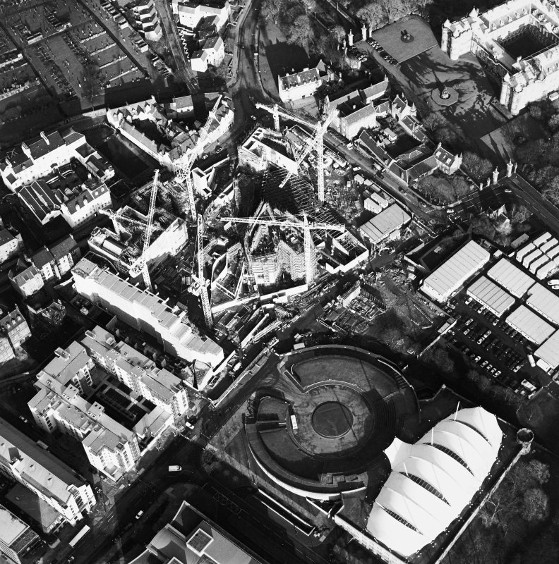 Oblique aerial view centred on the construction of the Scottish Parliament, with `Our Dynamic Earth', Queensberry House and Holyrood Palace adjacent, taken from the SSW.