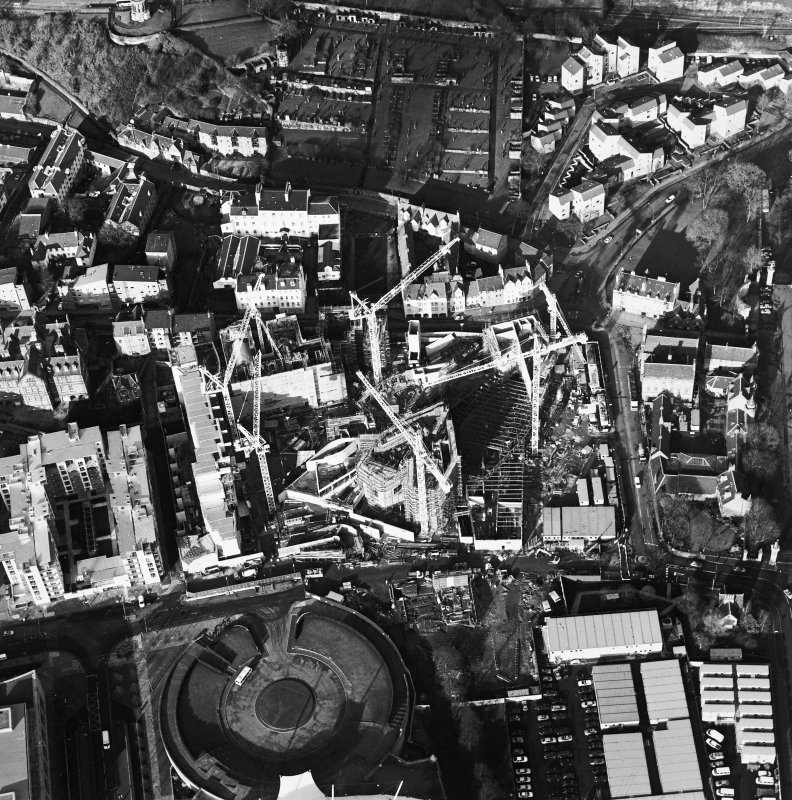 Oblique aerial view centred on the construction of the Scottish Parliament with `Our Dynamic Earth' and Queensberry House adjacent, taken from the SE.