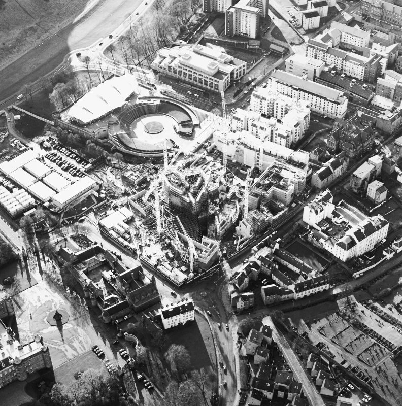 Oblique aerial view centred on the construction of the Scottish Parliament, with `Our Dynamic Earth', Queensberry House and Holyrood Palace adjacent, taken from the NNE.
