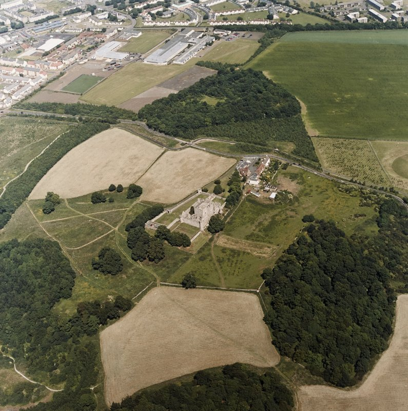 Oblique aerial view centred on the remains of the castle with the remains of the garden adjacent, taken from the SW.