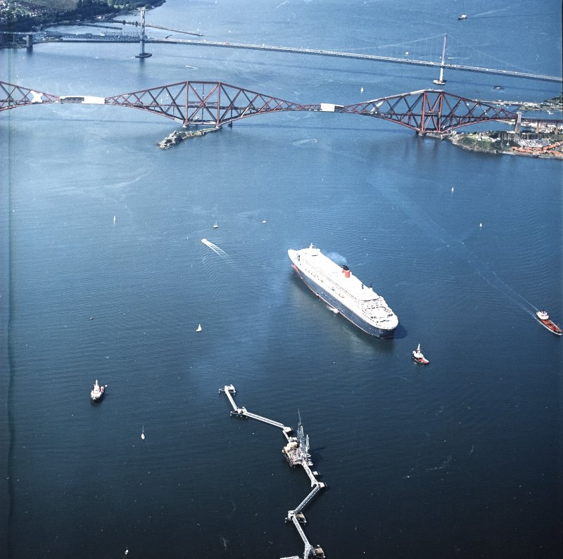 Oblique aerial view centred on the Queen Mary II cruise liner with road bridge and rail bridge adjacent, taken from the ENE.