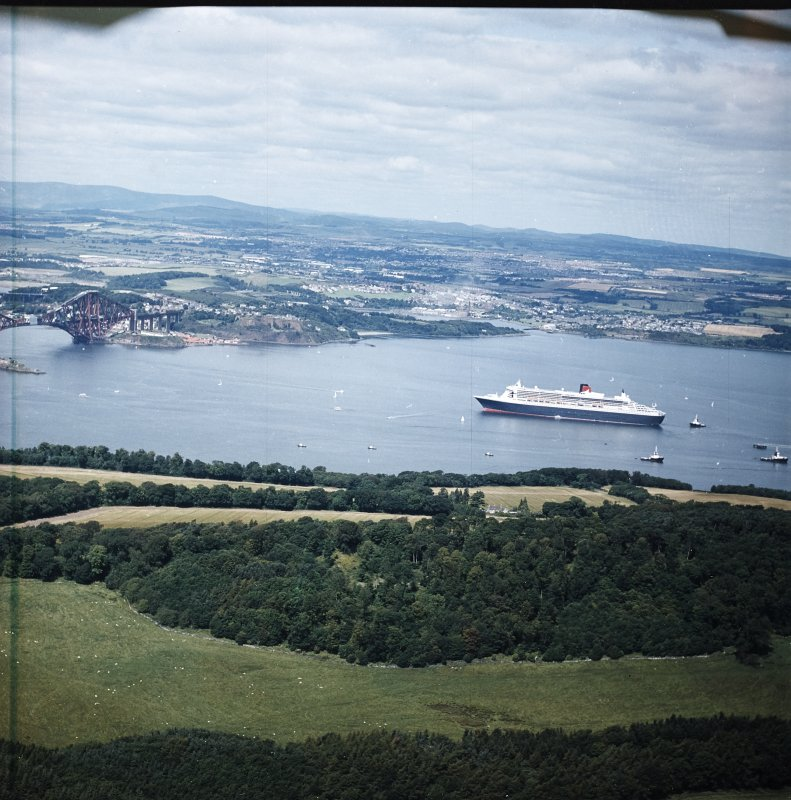 General oblique aerial view of the Queen Mary II cruise liner with rail bridge adjacent and Fife beyond, taken from the SE.