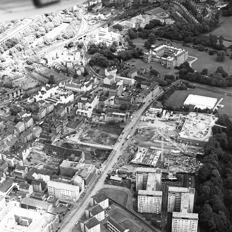 Oblique aerial view of Edinburgh centred on both 'Dynamic Earth' and the Scottish Parliament under construction, and a view of the Canongate, Holyrood Palace and Holyrood Abbey, taken from the SSW.