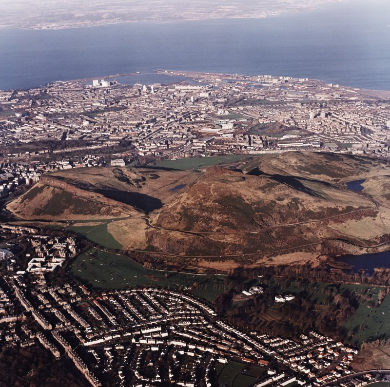 Oblique aerial view of Edinburgh centred on Holyrood Park, taken from the SSW.