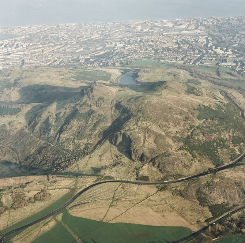 Oblique aerial view of Edinburgh, centred on Holyrood Park, taken from the SW.