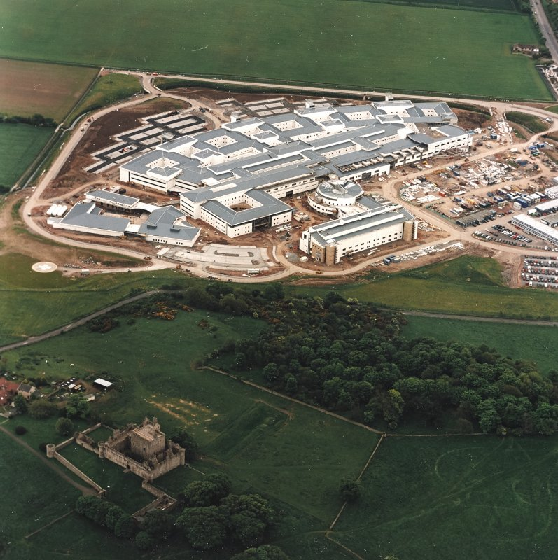 Oblique aerial view centred on the hospital with castle and garden adjacent, taken from the NW..