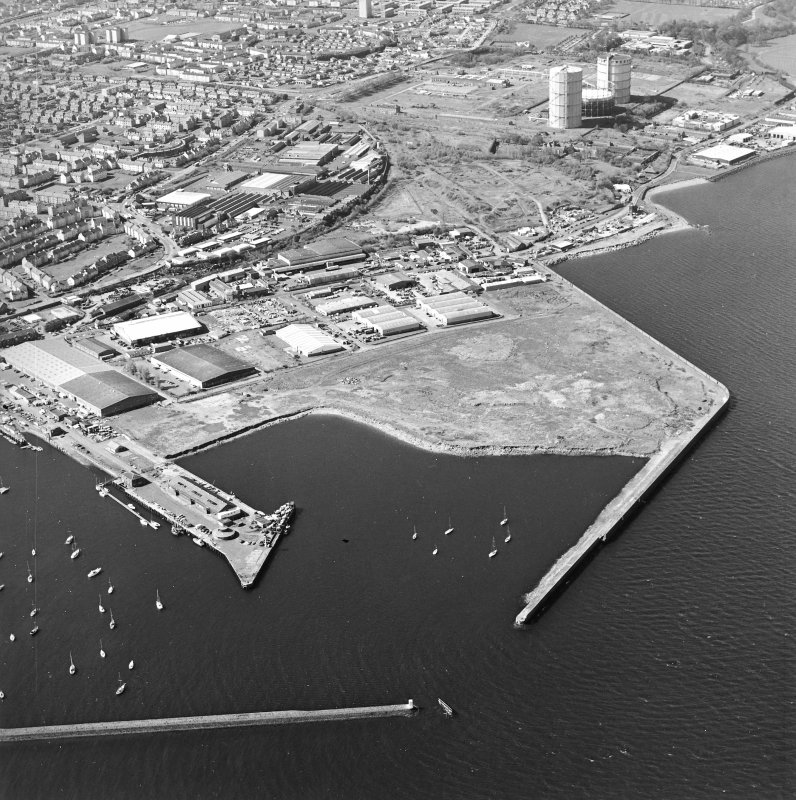 Oblique aerial view centred on the industrial estate with the office, works, harbour, and gas works adjacent, taken from the ENE.