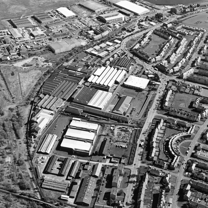 Oblique aerial view centred on the office and works with the industrial estate adjacent, taken from the SW.