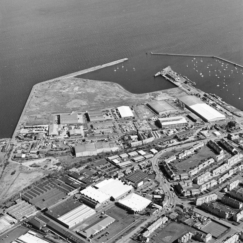 Oblique aerial view centred on the industrial estate with the office, works and harbour adjacent, taken from the SSW.
