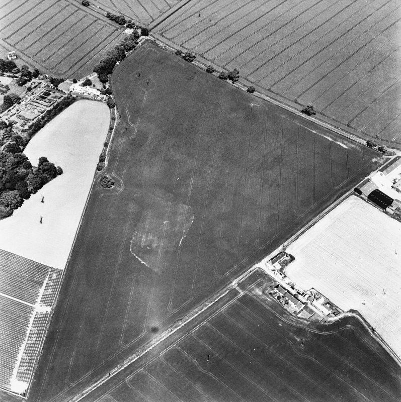 Oblique aerial view of Broomhouse taken from the SSW, centred on the cropmark of a quarry and a possible trackway, and showing Bourhouse Dovecot in the top left-hand corner of the photograph.