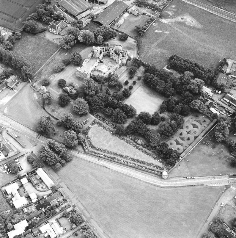 Dirleton Castle, oblique aerial view, taken from the WNW. The cropmark of a possible building is visible on Dirleton Village Green in the foreground.