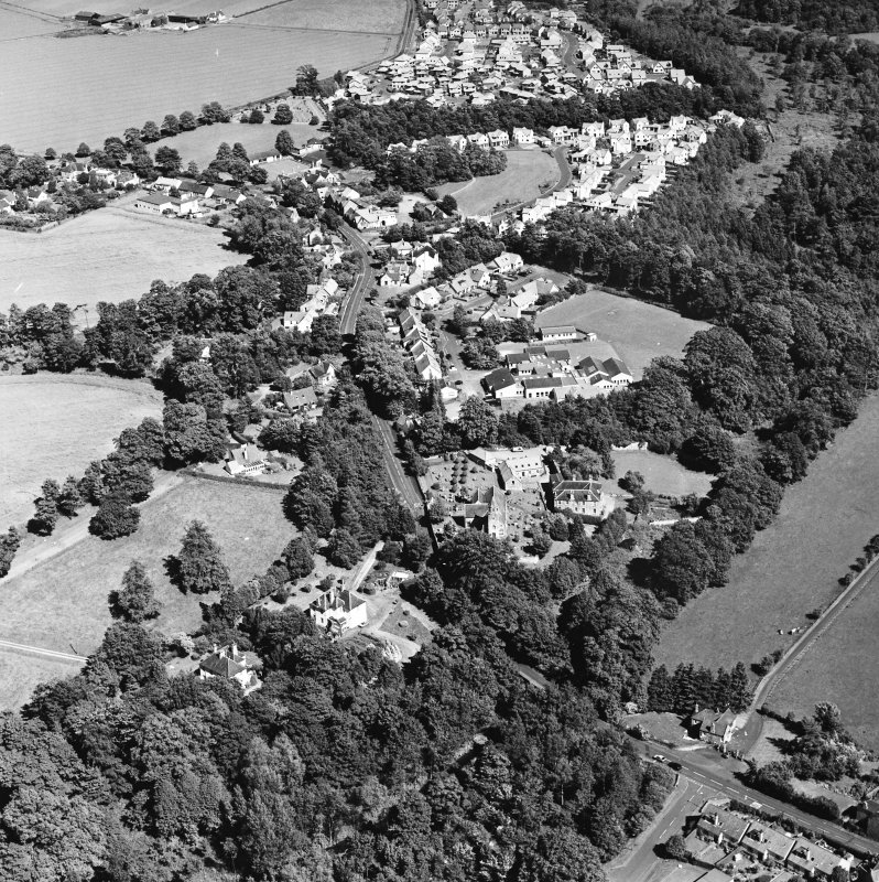 Oblique aerial view centred on the church, burial ground and village, taken from the WSW.