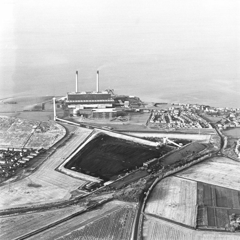 Oblique aerial view of the Cockenzie Coal Store centred on the coal store with an adjacent power station and harbour, taken from the SE.