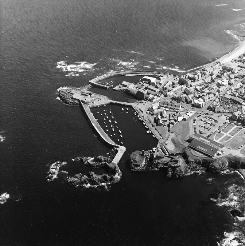 Oblique aerial view centred on the harbour with the remains of the battery adjacent, taken from the WNW.