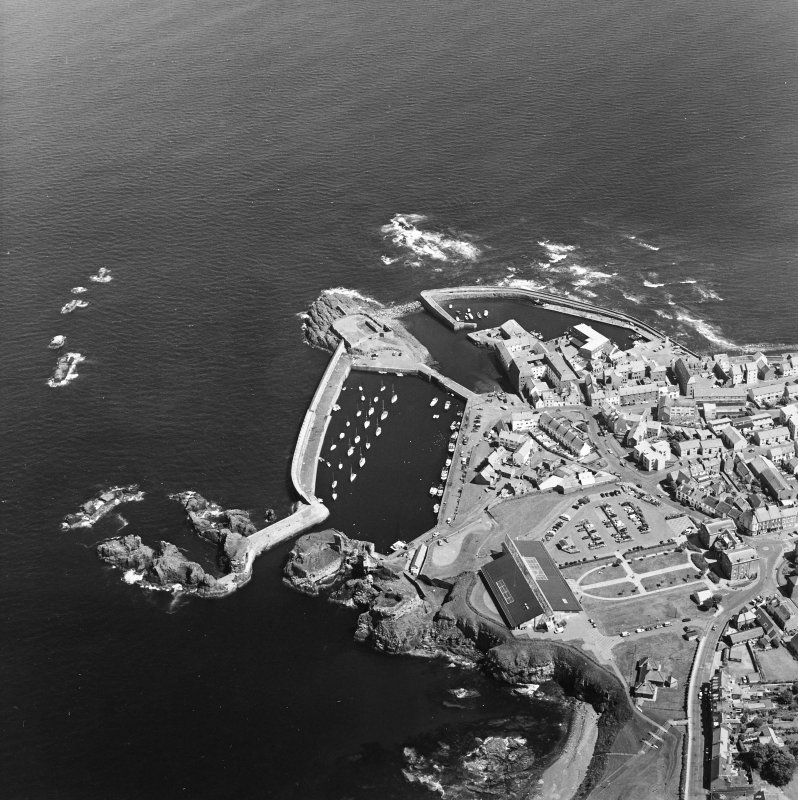 Oblique aerial view centred on the harbour with the remains of the battery adjacent, taken from the W.