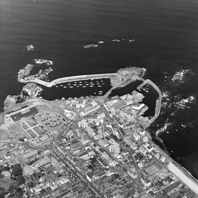 Oblique aerial view centred on the harbour with the remains of the battery adjacent, taken from the SSW.