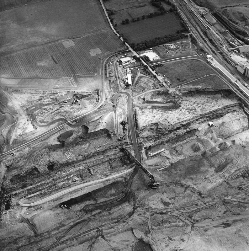 Oblique aerial view centred on the cement works and quarry with the trial excavations adjacent, taken from the NW.