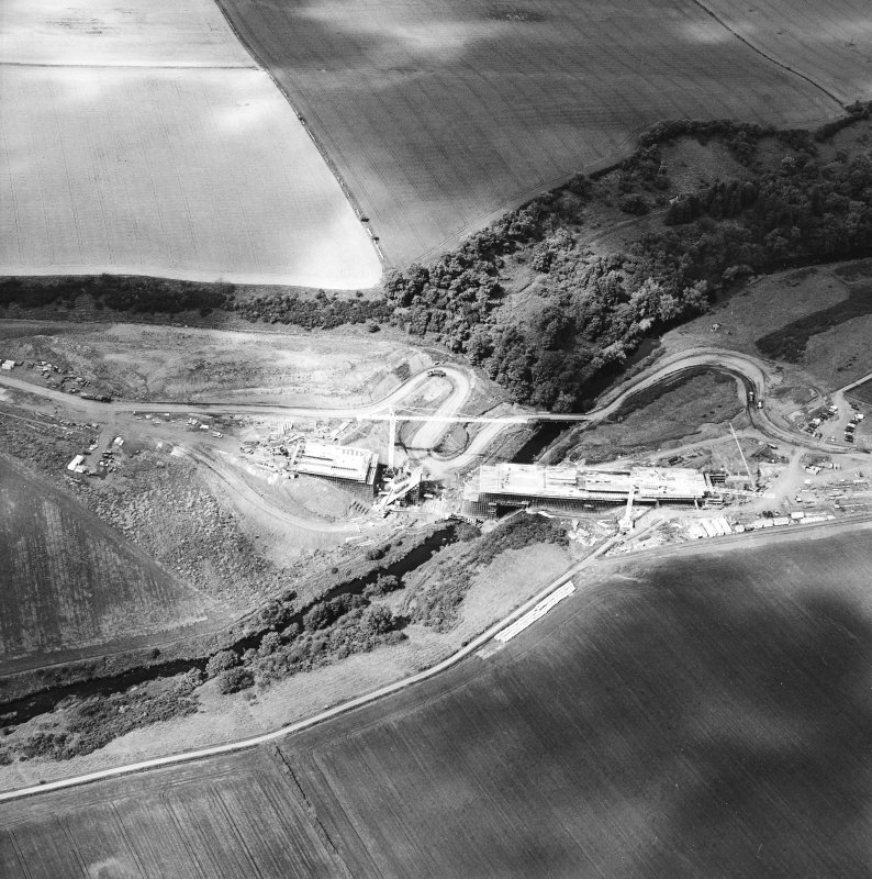 Oblique aerial view centred on the construction of the bridge, taken from the S.