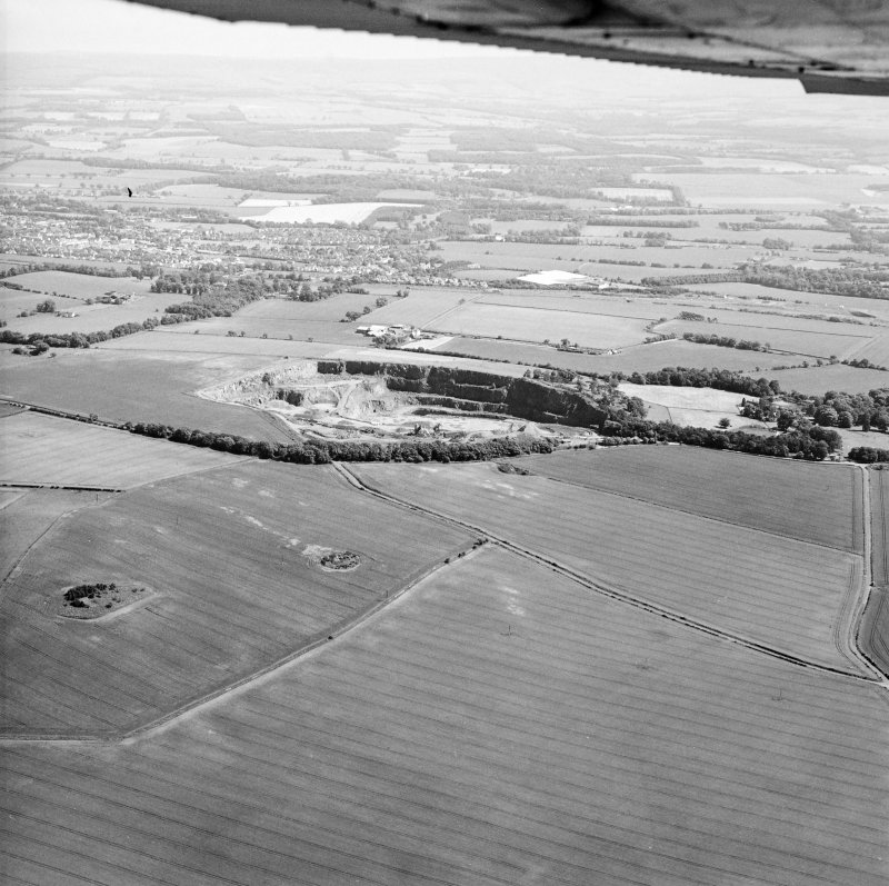 Oblique aerial view centred on the quarry, taken from the NW.