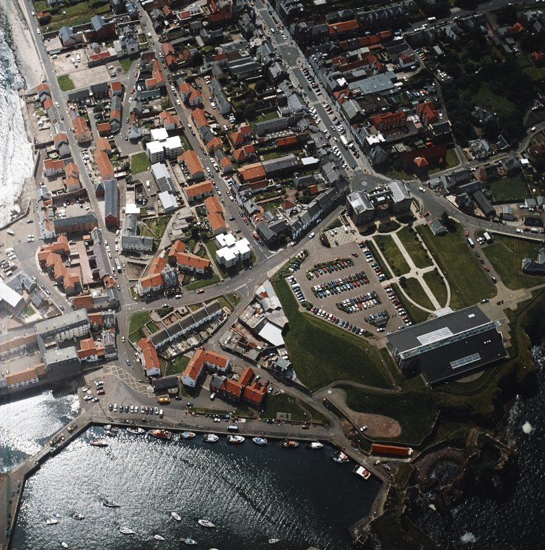 Oblique aerial view centred on fishermen's housing at Victoria Place, barracks and leisure centre with the harbour and castle adjacent, taken from the N.