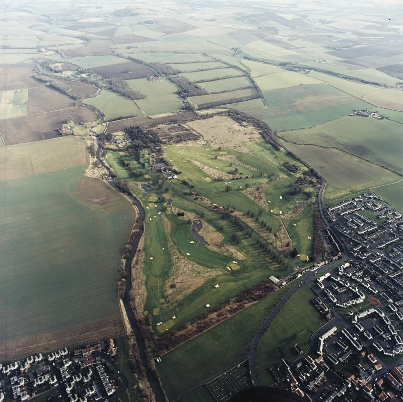 Oblique aerial view centred on the golf course, club house and walled garden, taken from the W.