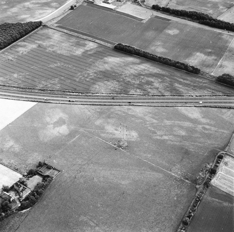 Monkton House and Newton, oblique aerial view, taken from the WNW, centred on a series of cropmarks including those of a pit-alignment. Monkton House is visible in the bottom left-hand corner of the photograph.