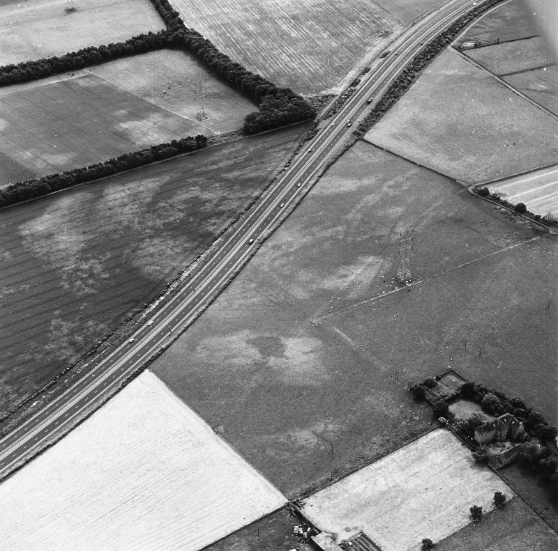 Monkton House and Newton, oblique aerial view, taken from the N, centred on a series of cropmarks including those of a pit-alignment. Monkton House is visible in the bottom right-hand corner of the photograph.