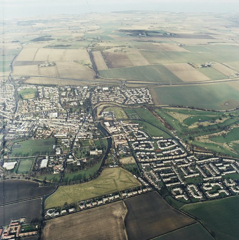 General oblique aerial view of Haddington centred on the church, grain mills, maltings and bridges with golf course adjacent, taken from the SSE.