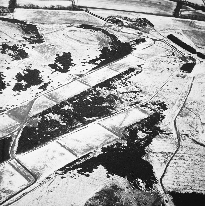 Oblique aerial view centred on the rifle range with the farmhouse and farmsteading and the remains of the fort, trenches and rig adjacent, taken from the WNW.