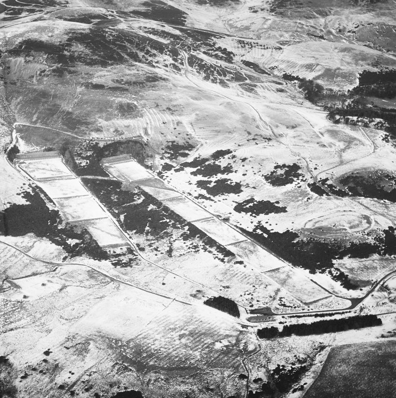 General oblique aerial view centred on the rifle range with the remains of the fort, trenches and rig adjacent, taken from the SSW.