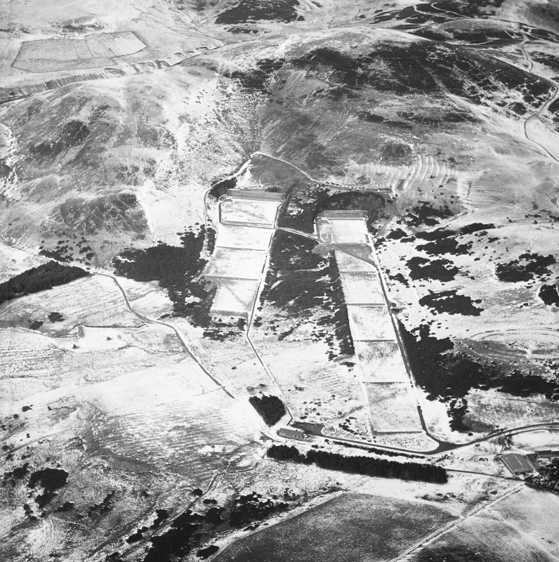 General oblique aerial view centred on the rifle range with the remains of the fort, trenches, ring-ditch house and rig adjacent, taken from the SSE.
