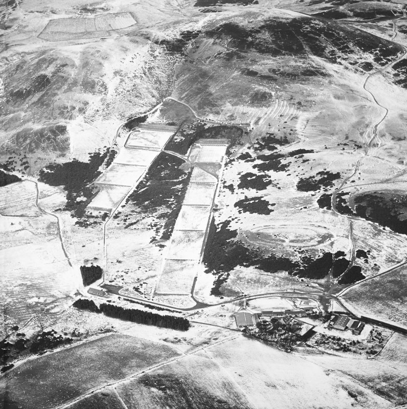 General oblique aerial view centred on the rifle range with the farmhouse and farmsteading and the remains of the fort, trenches, ring-ditch house and rig adjacent, taken from the SSE.