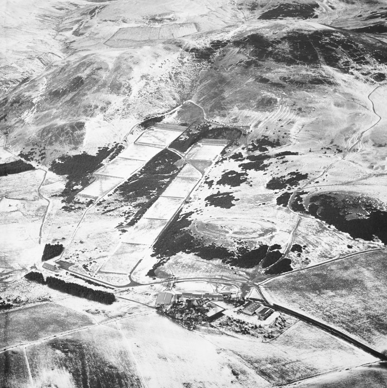 General oblique aerial view centred on the rifle range with the farmhouse and farmsteading and the remains of the fort, trenches, ring-ditch house and rig adjacent, taken from the SE.