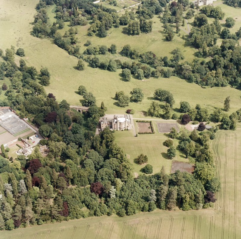Oblique aerial view, taken from the SW, centred on Oxenfoord Castle.  Preston Hall is also visible in the top right hand corner of the photograph.