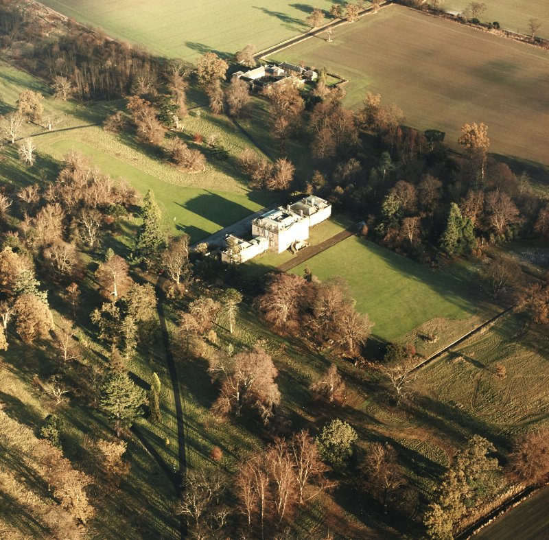 Preston Hall, oblique aerial view, taken from the SW, centred on the country house with the stables in the top centre of the photograph.