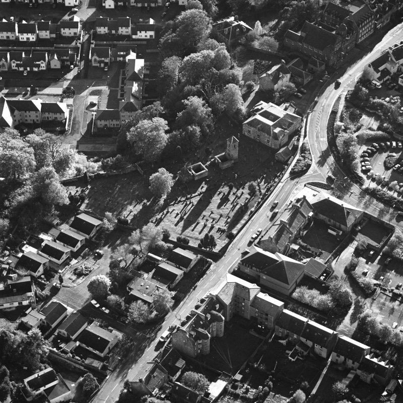 Oblique aerial view of Penicuik, ST Kentigern's Church and Churchyard centred on a church, churchyard and burial ground, with a mausoleum and other church and hearse house adjacent, taken from the N.