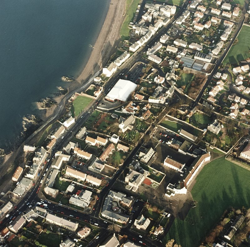 Oblique aerial view of Prestonpans, Kirk Street, Prestongrange Church centred on a church and graveyard, taken from the SW.