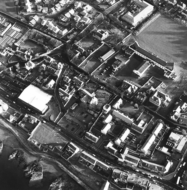 Oblique aerial view of Prestonpans, Kirk Street, Prestongrange Church centred on a church and graveyard, taken from the NW.