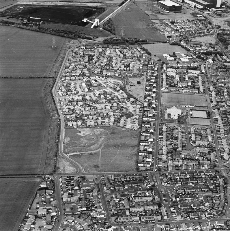 Oblique aerial view centred on the housing estate constructed on the site of two former settlements, taken from the E.
