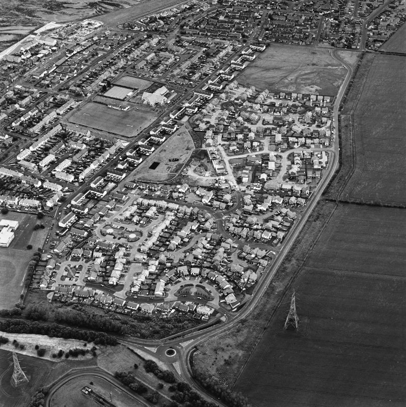 Oblique aerial view centred on the housing estate constructed on the site of two former settlements, taken from the NE.