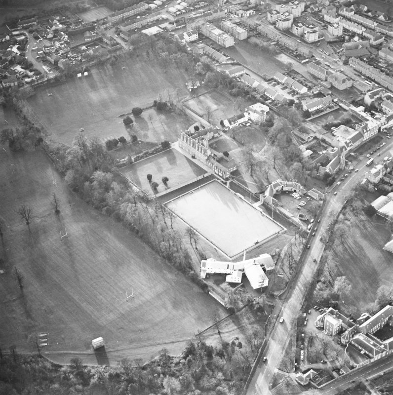 Oblique aerial view centred on the tower-house, school and garden, taken from the NE.