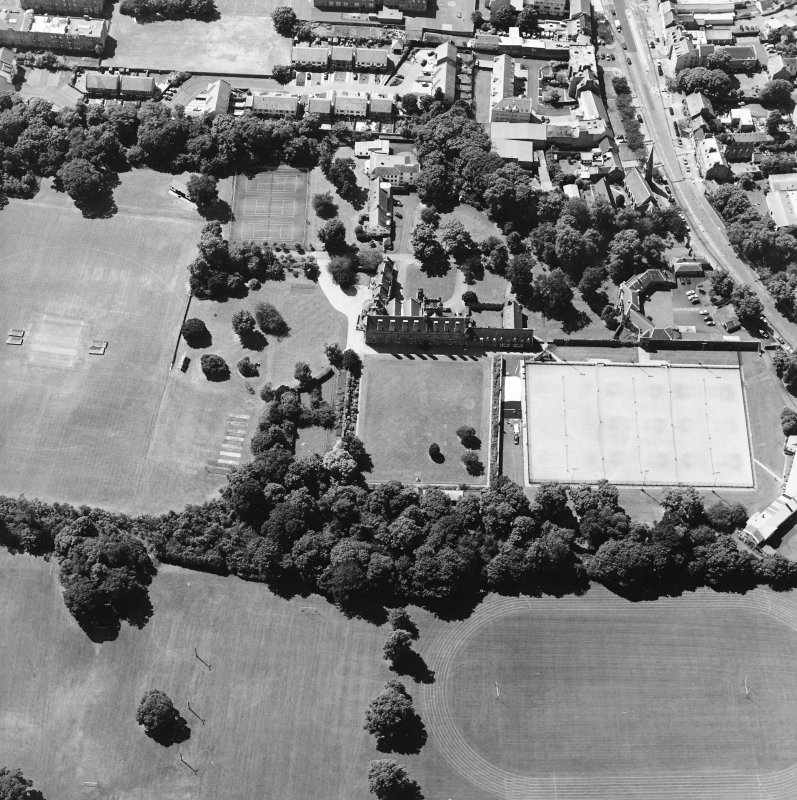 Oblique aerial view centred on the garden with the tower-house and school adjacent, taken from the E.