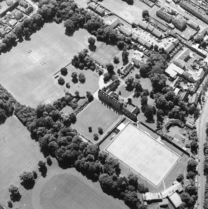 Oblique aerial view centred on the garden with the tower-house and school adjacent, taken from the NE.