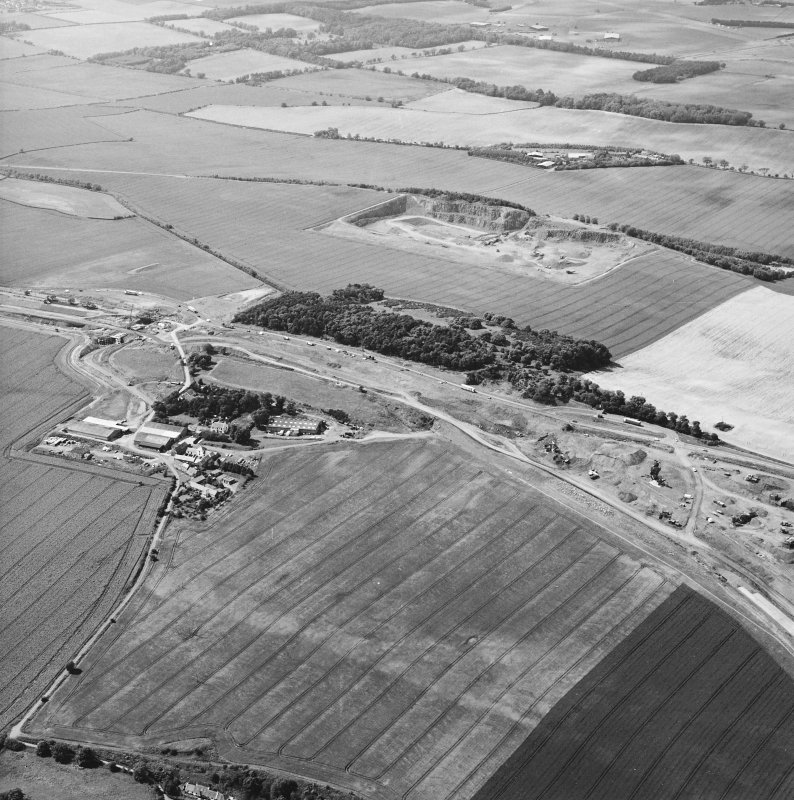 Oblique aerial view centred on the road construction and the quarry, with the farmhouses, farmsteading and cottages adjacent, taken from the SE.