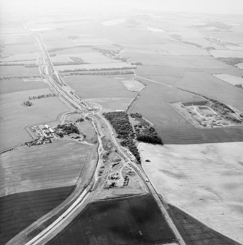 Oblique aerial view centred on the road construction with the quarry, farmhouse, farmsteading and cottages adjacent, taken from the E.