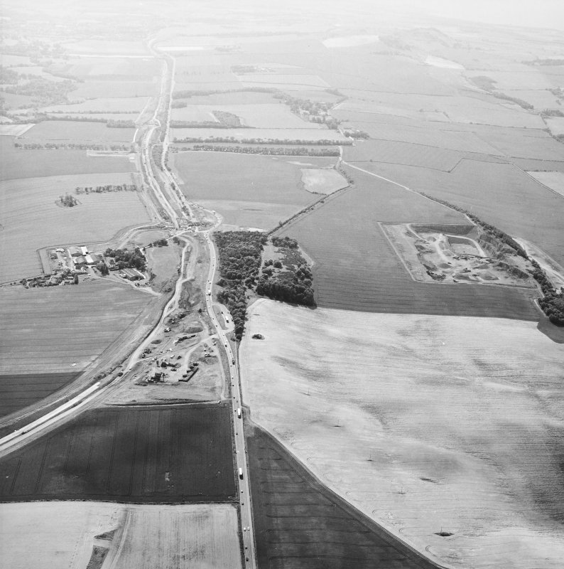 Oblique aerial view centred on the road construction with the quarry, farmhouse, farmsteading and cottages adjacent, taken from the ENE.